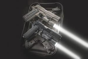 two handguns on a range bag with weapon lights fitted to the rail