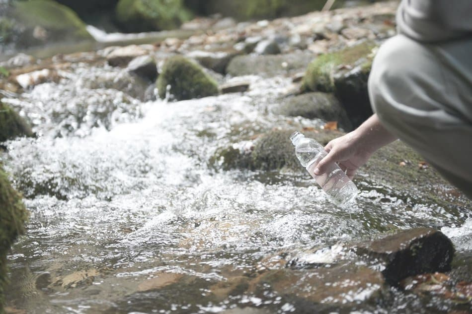 man gathering water for survival from a stream in the woods