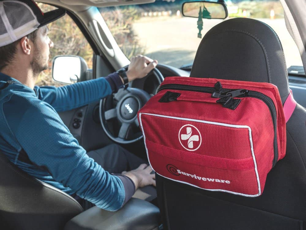 large first aid kit hung from car seat headrest