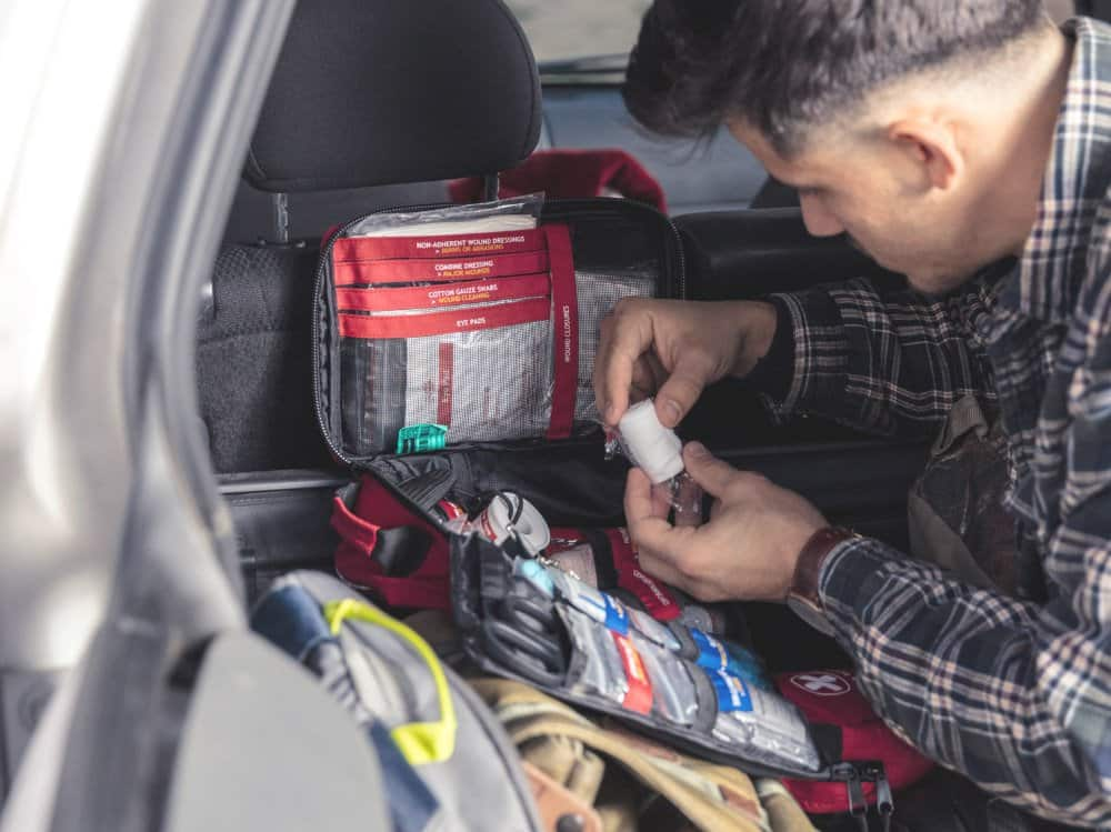 man looking for bandage in large first aid kit