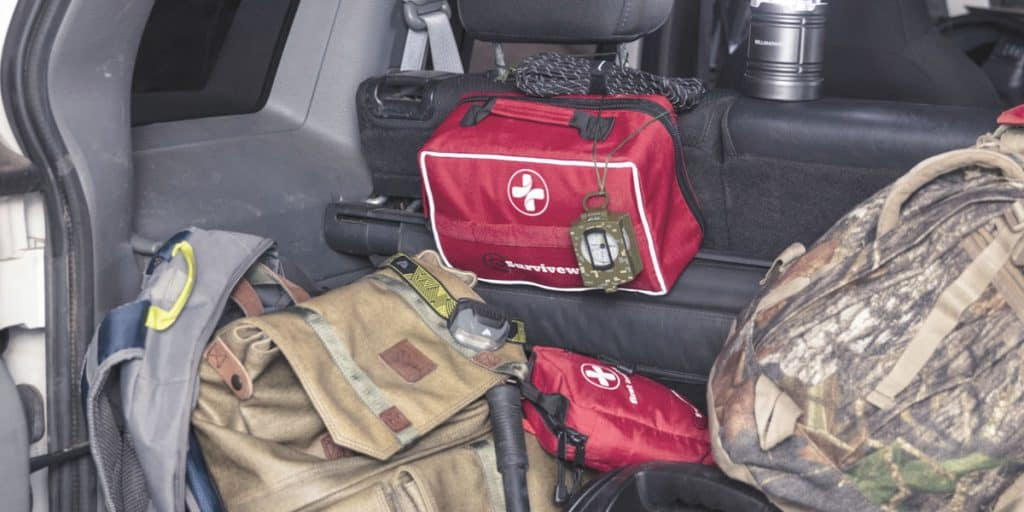 large first aid kit in trunk of car next to small first aid kit
