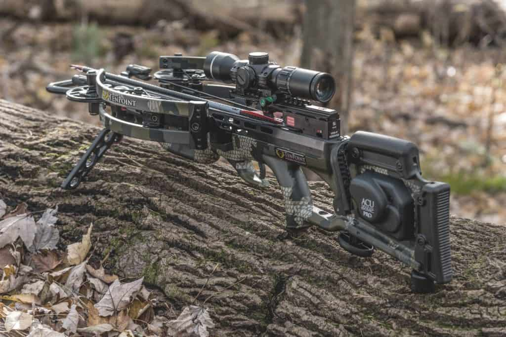 a crossbow resting on a fallen tree trunk in the woods
