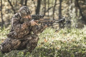 hunter in forest taking aim using the tenpoint invader x4 crossbow