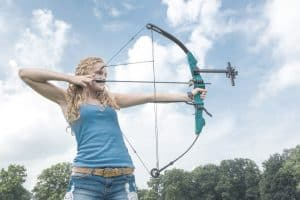 woman holding a beginner compound bow taking aim at her target