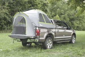 pickup truck on camping ground with a truck tent camper on the rear bed