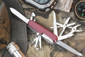 swiss army knife multi tool sat along side survival gear