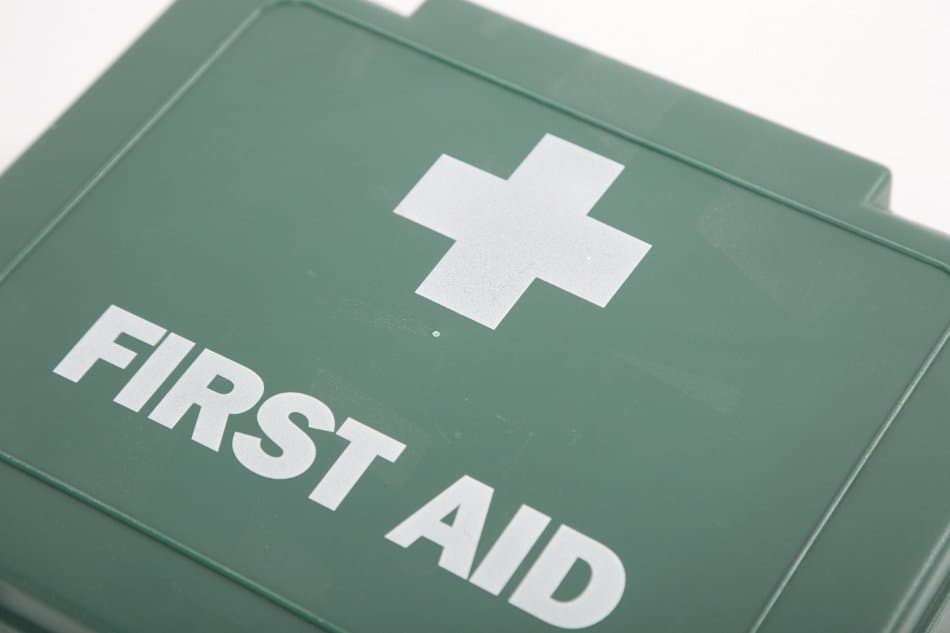green plastic UK first aid box with white cross and first aid text