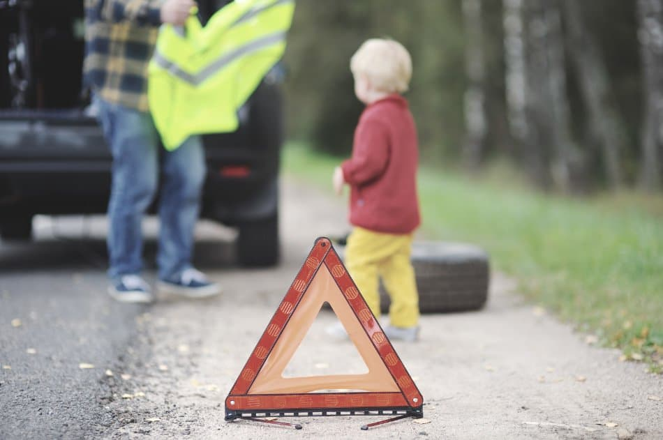 father puts safety vest on child after car breakdown emergency