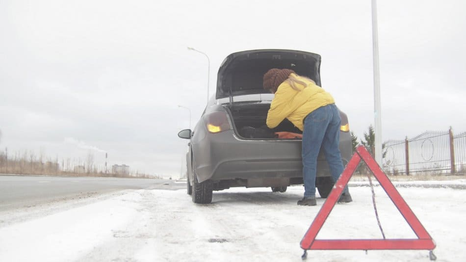 woman looking for goods in her trunk of broken down car in the snow