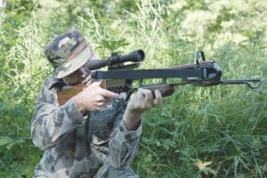 a hunter holding and firing a recurve crossbow outdoors