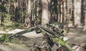 first person view on a huner holding a tactical crossbow in a forest