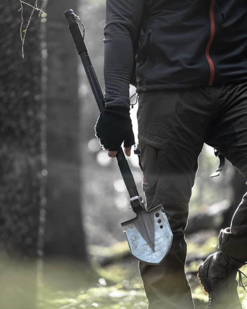 survival shovel in mans hand