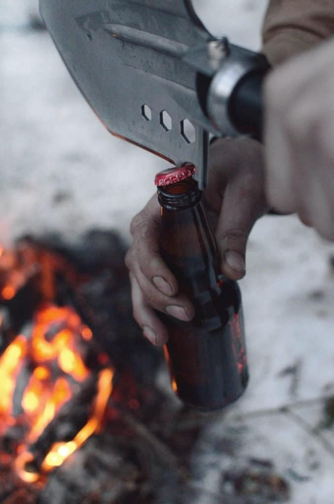 survival shovel being used to open a beer bottle top