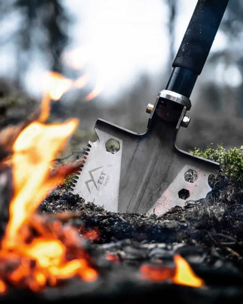 survival shovel being used to dig a hole for a fire pit