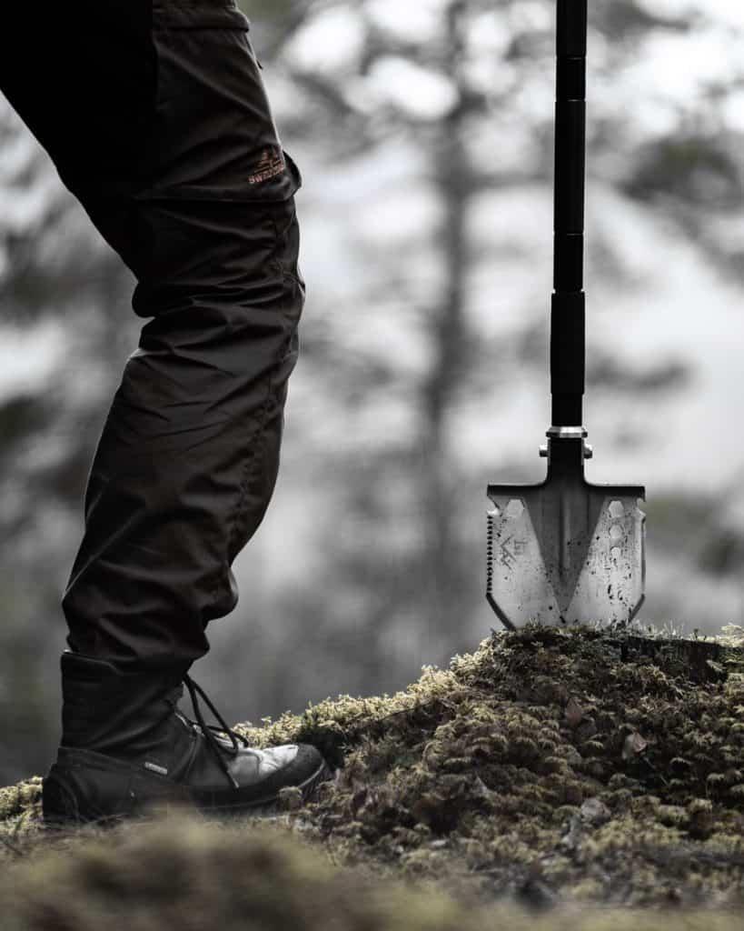 man holding survival shovel wedged into tree stump