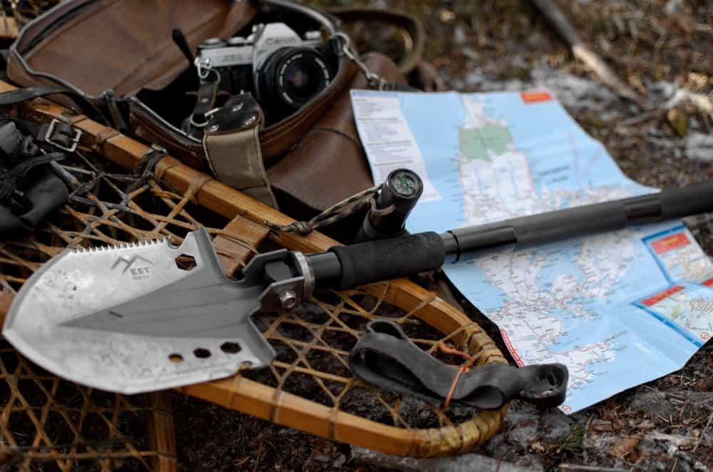 survival shovel on woodland ground among other camping gear