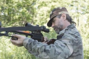 hunter in the woods taking aim with a crossbow
