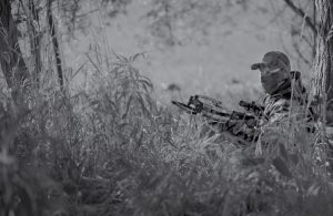 crossbow hunter sitting in long grass waiting for his prey