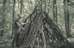 man building a survival shelter in the forest using tree branches and leaves