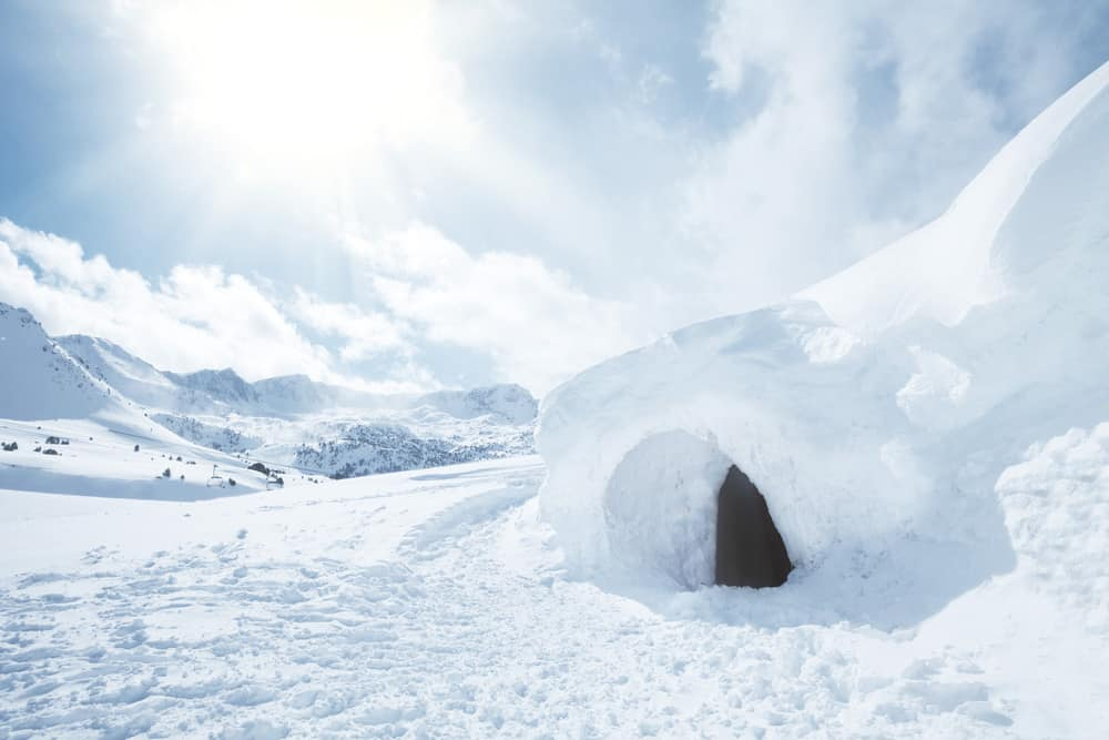 snow cave survival shelter against a snow mountain