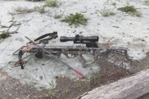 crossbow laid on ground in a safe position with arrows beside it