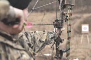 man taking aim at a target in the bush with a compound bow