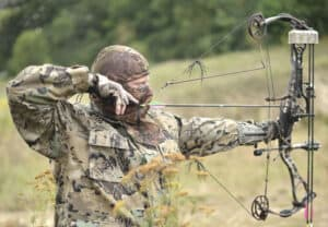hunter in field taking aim with his compound bow