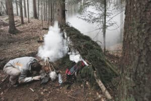 man lighting emergency fire using his survival resources to stay alive